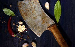 Sharp butcher knife lying on butcher block with vegetables. Whetstone sharpening.