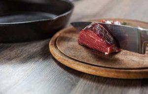 Sharp knife cutting rare steak. Whetstone sharpening.